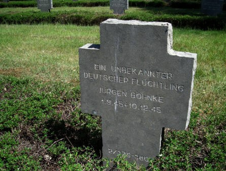 The grave of an unknown and a known German refuge at Grove War Cemetery.