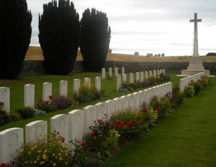Some of the British World War I graves located on the Quatre Vents Military Cemetery in Estree-Cauchy - and the big white cross at the end of the cemetery.