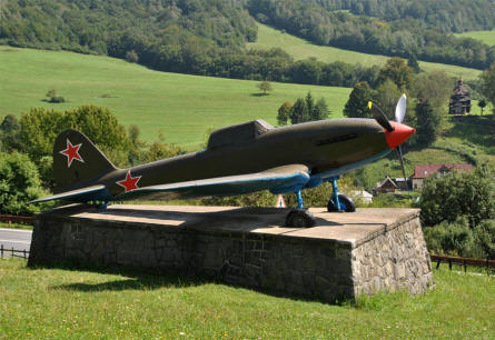 A Russian World War II IL-2 Sturmovik displayed along the main road thru the Dukla Pass. In the background one of the many historic wooden churches that are located in this area.
